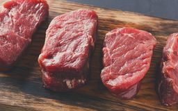 Raw beef filet mignon steaks on wooden board at gray background. Raw filet mignon steaks. Slices of fresh beef meat arranged in a row on wooden cutting board at royalty free stock photography