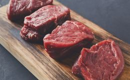 Raw beef filet mignon steaks on wooden board at gray background. Raw filet mignon steaks. Slices of fresh beef meat arranged in a row on wooden cutting board at Stock Photography