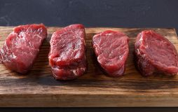 Raw beef filet mignon steaks on wooden board at gray background. Raw filet mignon steaks with spices closeup. Slices of fresh beef meat arranged in a row on stock photography