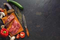 Raw beef filet mignon steaks on wooden board. Raw filet mignon steaks closeup. Fresh beef meat, rosemary and knife on wooden board at black background. Organic Royalty Free Stock Photos