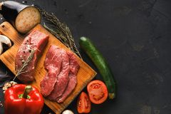 Raw beef filet mignon steaks on wooden board. Raw filet mignon steaks closeup. Fresh beef meat, rosemary on wooden board at black background. Organic ingredients Royalty Free Stock Images