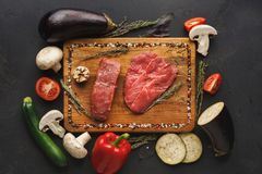 Raw beef filet mignon steaks on wooden board. Raw filet mignon steaks closeup. Fresh beef meat, rosemary on wooden board at black background. Organic ingredients Stock Photography