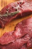 Raw beef filet mignon steaks on wooden board. Raw filet mignon steaks closeup. Fresh beef meat, rosemary on wooden board, kitchen background. Organic ingredients stock photo