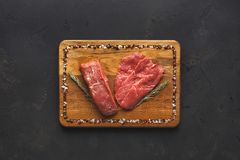 Raw beef filet mignon steaks on wooden board. Raw filet mignon steaks. Fresh beef meat, rosemary on wooden board at black background. Organic ingredients for Stock Images