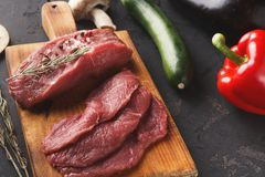 Raw beef filet mignon steaks on wooden board. Raw filet mignon steaks. Fresh beef meat, rosemary on wooden board at black background. Organic ingredients for royalty free stock photo