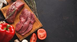 Raw beef filet mignon steaks on wooden board. Raw filet mignon steaks. Fresh beef meat, rosemary on wooden board at black background. Organic ingredients for royalty free stock photography