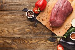 Raw beef filet mignon steaks on wooden board. Raw filet mignon steaks. Fresh beef meat, rosemary on wooden board, kitchen background. Organic ingredients for royalty free stock photography