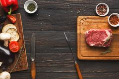 Raw beef filet mignon steaks on wooden board. Raw filet mignon steaks. Fresh beef meat on wooden board at black background with fork and knife. Organic Stock Image