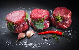Raw beef fillet steaks mignon on dark background. Raw beef fillet steaks mignon with spices on dark background stock photos