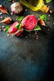 Raw beef fillet steaks mignon. With spices and herbs on dark concrete table background royalty free stock photo