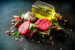 Raw beef fillet steaks mignon. With spices and herbs on dark concrete table background stock photos