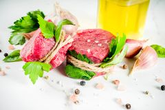 Raw beef fillet steaks mignon. With spices and herbs on white marble table background royalty free stock photography