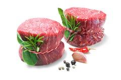 Raw beef fillet steaks mignon  on white background. Raw beef fillet steaks mignon with spices  on white background Stock Photos