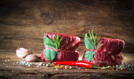 Raw beef fillet steaks mignon on wooden background. Raw beef fillet steaks mignon with spices on wooden background Stock Images