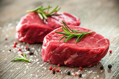 Raw beef fillet steaks with spices. On wooden background Royalty Free Stock Photos