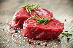 Raw beef fillet steaks with spices. On wooden background Royalty Free Stock Photography