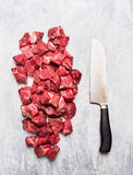 Raw beef goulash meat diced for stew with meat knife on light gray wooden background. Top view royalty free stock images