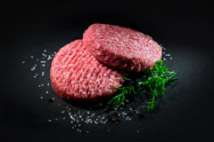 Raw beef hamburger patties with spices. On dark slate plate Stock Images