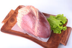 Raw beef heart and lettuce leaf on wooden desk isolated on white background from above and copy space. ready for cooking Royalty Free Stock Photography
