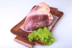 Raw beef heart and lettuce leaf on wooden desk isolated on white background from above and copy space. ready for cooking Stock Photo