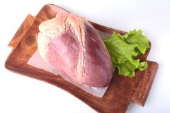 Raw beef heart and lettuce leaf on wooden desk isolated on white background from above and copy space. ready for cooking Royalty Free Stock Photos