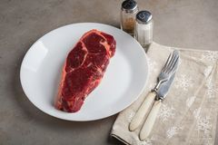 Raw beef marbled steak with vintage white utensils on old stone background. A piece of meat with pepper and salt on the table. Ste. Ak New York. Top view Royalty Free Stock Image
