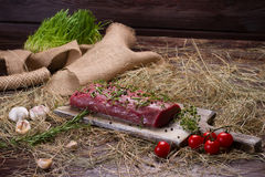 Raw beef marinated in spices. Meat with tomatoes and garlic on the hay Royalty Free Stock Image
