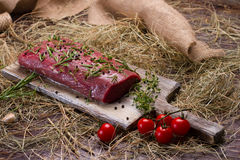 Raw beef marinated in spices with tomato. Meat on a cutting board Stock Photo