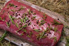 Raw beef marinated in spices. Raw beef marinated in spices on the wooden board. Meat close-up Royalty Free Stock Images