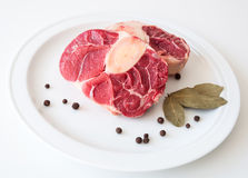 Raw beef meat. Shin of raw beef meat on a white plate with peppers and laurel leaves Stock Photos