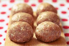 Raw beef meat balls. Six pork balls from minced meat laid on wooden cutting board Stock Image