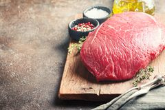 Raw beef meat. Big cut of raw beef meat with thyme, garlic and spices over dark brown background Stock Photography