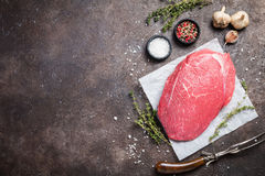 Raw beef meat. Big cut of raw beef meat with thyme, garlic and spices over dark brown background, top view Royalty Free Stock Photos