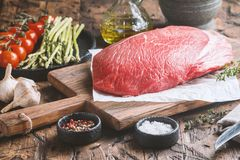 Raw beef meat. Big cut of raw beef meat with thyme, garlic and spices on a wooden background Stock Images