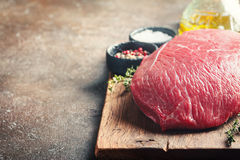 Raw beef meat. Big cut of raw beef meat with thyme, garlic and spices over dark brown background Stock Photos