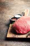 Raw beef meat. Big cut of raw beef meat with thyme, garlic and spices over dark brown background Stock Photo