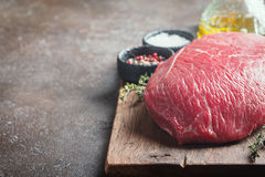 Raw beef meat. Big cut of raw beef meat with thyme, garlic and spices over dark brown background Stock Images