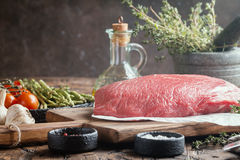 Raw beef meat. Big cut of raw beef meat with thyme, garlic and spices on a wooden background Royalty Free Stock Photography
