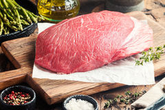 Raw beef meat. Big cut of raw beef meat with thyme, garlic and spices on a wooden background Stock Photos
