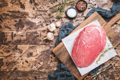 Raw beef meat. Big cut of raw beef meat with thyme, garlic and spices on a wooden background, top view Royalty Free Stock Image