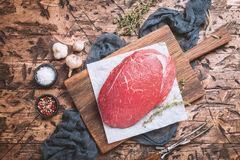 Raw beef meat. Big cut of raw beef meat with thyme, garlic and spices on a wooden background, top view Royalty Free Stock Photos