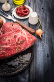 Raw Beef meat in black pan with seasonings and sauce on blue wooden table, preparation Royalty Free Stock Photos