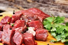 Raw beef meat. Coriander and pepper on cutting board Stock Image