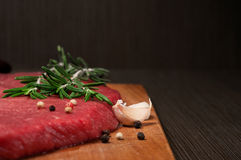 Raw beef meat on a cutting board. Close up raw beef meat on a cutting board with a sprig of rosemary, garlic and peppercorn. Copy space Royalty Free Stock Photos