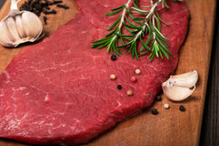Raw beef meat on a cutting board. Close up raw beef meat on a cutting board with a sprig of rosemary, garlic and peppercorn. Top view with copy space Stock Image