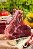 Raw beef meat on cutting board and fresh vegetables. On wooden table Stock Photography