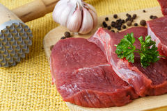 Raw beef meat on a cutting board. Raw beef meat and garlic on a cutting board Stock Images