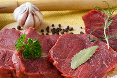Raw beef meat on a cutting board. Raw beef meat and garlic on a cutting board Royalty Free Stock Photo