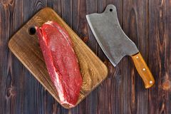 Raw beef meat on cutting board with old vintage cleaver.  Stock Photos