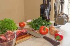 Raw beef meat on a cutting board. Preparing meal, meat and vegetables Royalty Free Stock Photography